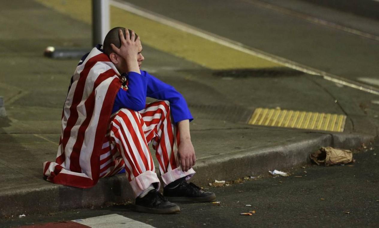 Homem vestido com as cores da bandeira americano senta sozinho na calçada em protesto contra presidente eleito, Donald Trump, em Seattle Foto: Ted S. Warren / AP