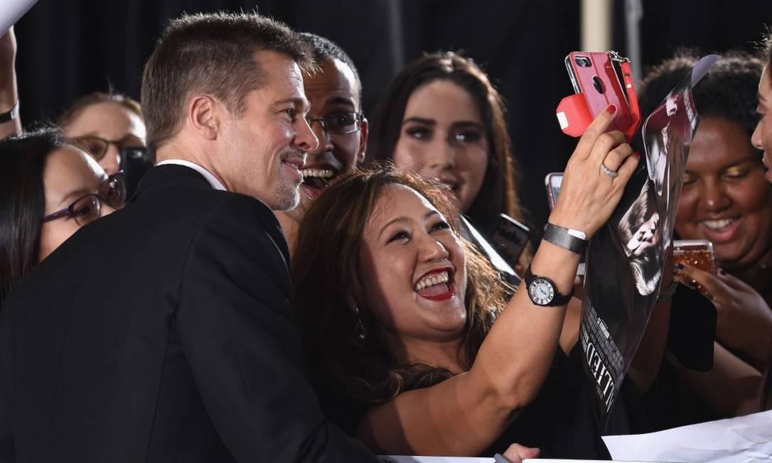 Apesar dos problemas pessoais, Brad Pitt fez questão de ser solícito tirar selfies com os fãs Frazer Harrison / AFP