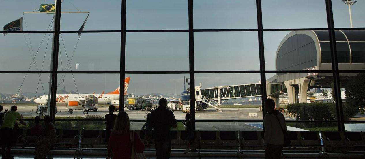 Passageiros observam a movimentação de aviões no saguão do Aeroporto Santos Dumont Foto: Antonio Scorza / Agência O Globo 19-6-2016