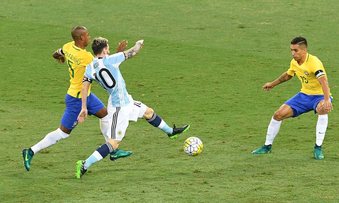 Messi tenta passar por Fernandinho e Marquinhos no Mineirão EVARISTO SA / AFP