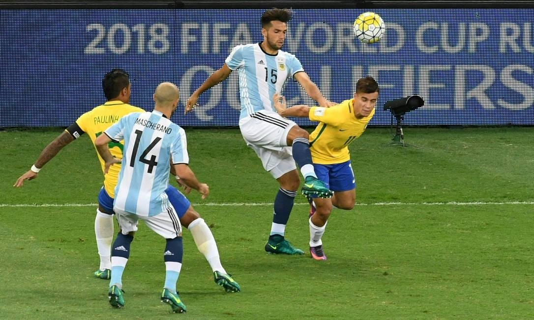 Philippe Coutinho disputa a bola com o argentino Mas no Mineirão, observados por Paulinho e Mascherano EVARISTO SA / AFP