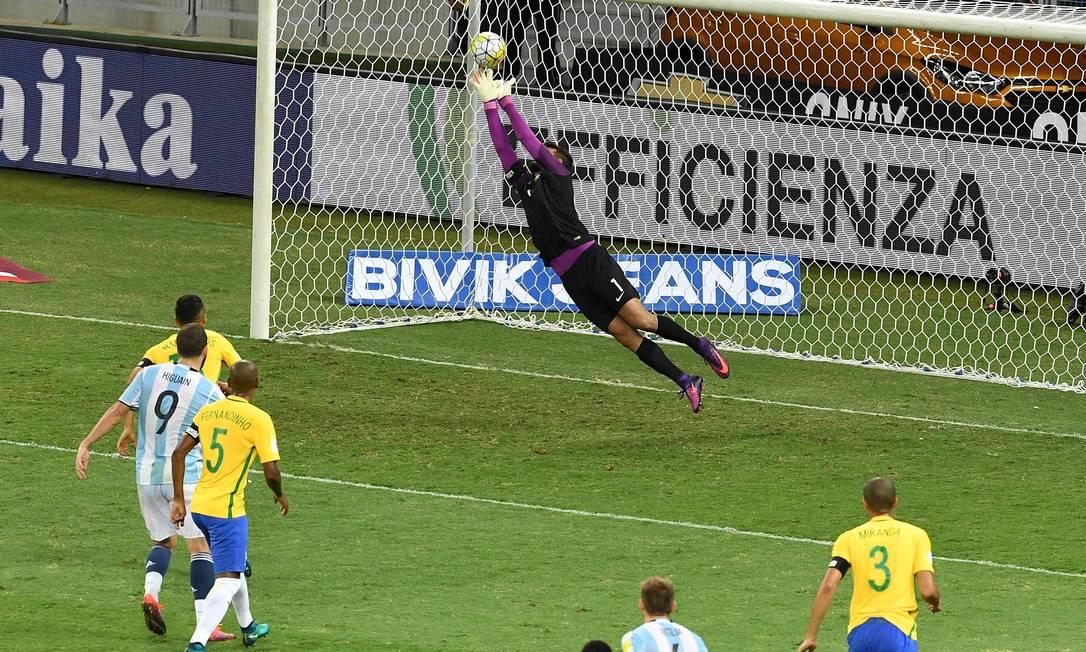 Goleiro Alisson voa e espalma bola chutada por Biglia, número 6 EVARISTO SA / AFP