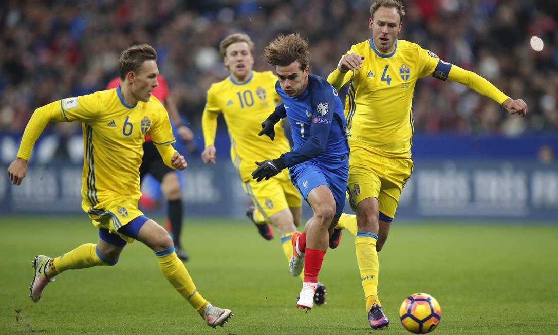 O artilheiroGriezmann (7) se projeta entre três jogadores da Suécia: França jogando em casa Christophe Ena / AP