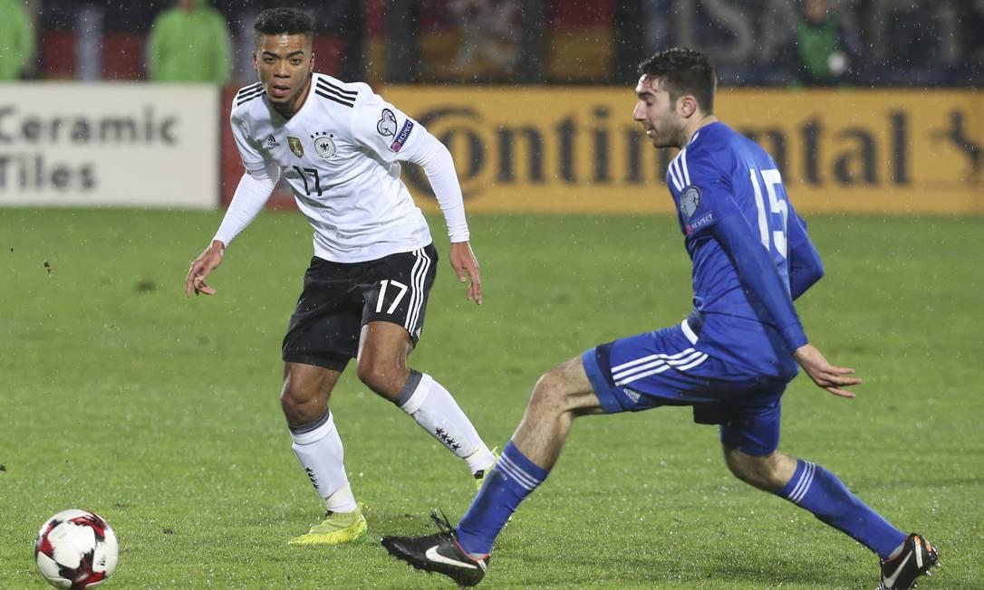 O alemão Henrichs (17) observa com atenção o movimento da bola, diante de Marco Berardi, de San Marino STEFANO RELLANDINI / REUTERS