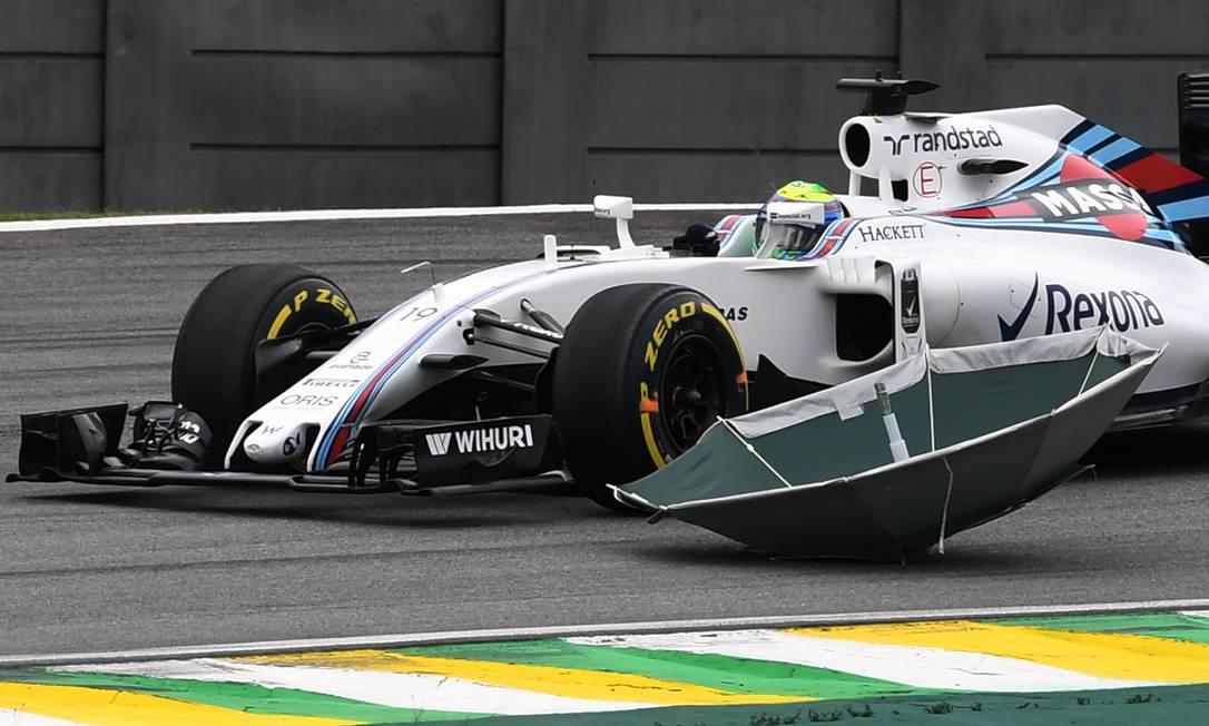 Um guarda-chuva voa para perto do carro de Felipe Massa durante os treinos da F-1 VANDERLEI ALMEIDA / AFP