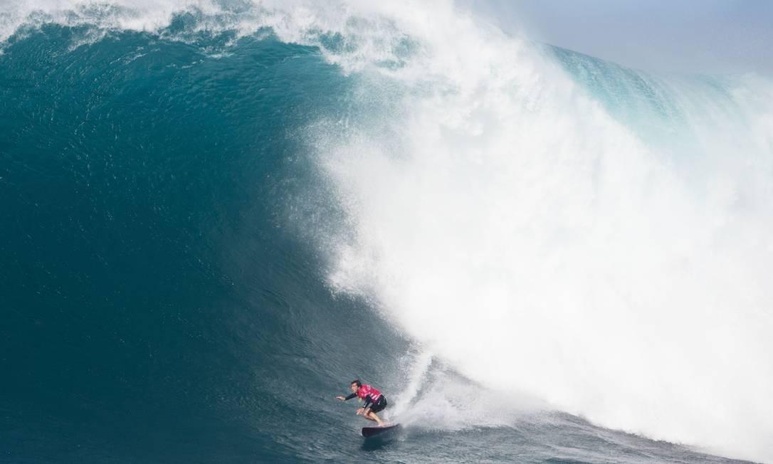 O californiano Greg Long surfa uma grande onda em Jaws, na costa da ilha Maui, no Avaí Foto: BRIAN BIELMANN / AFP