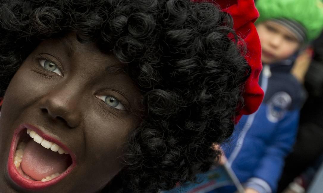 Uma pessoa pintada de negro representando Black Pet, ajundante de São Nicolau (o precursor de Papai Noel ), interage com crianças, na Holanda Foto: Peter Dejong / AP