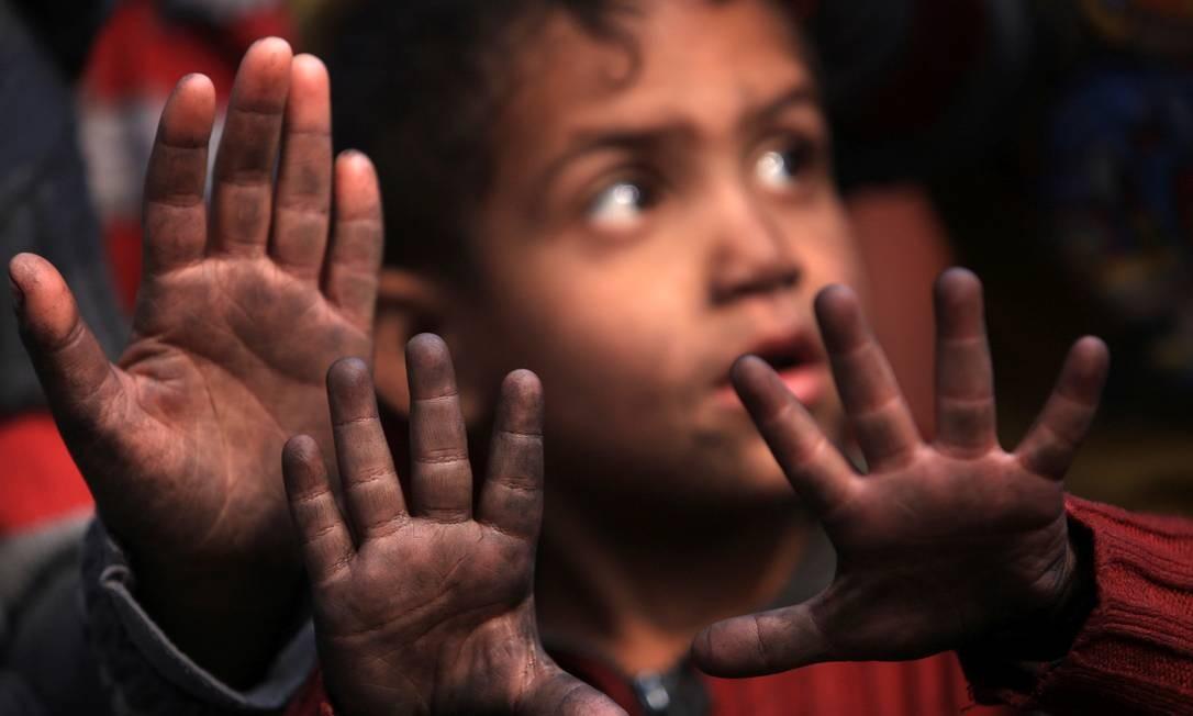 Crianças mostram as mãos sujas de óleo de uma instalação de petróleo incendiada pelo Estado Islâmico, em Qayyara, no Iraque Foto: ARI JALAL / REUTERS