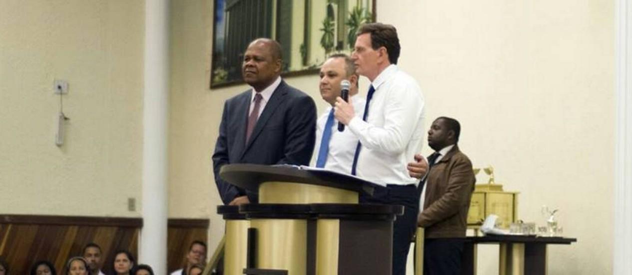 Agradecimento. Ao lado do vereador João Mendes de Jesus (esquerda) e do pastor Carlos Azevedo, Crivella fala para fieis numa Igreja Universal em Inhaúma Foto: Reprodução/Facebook