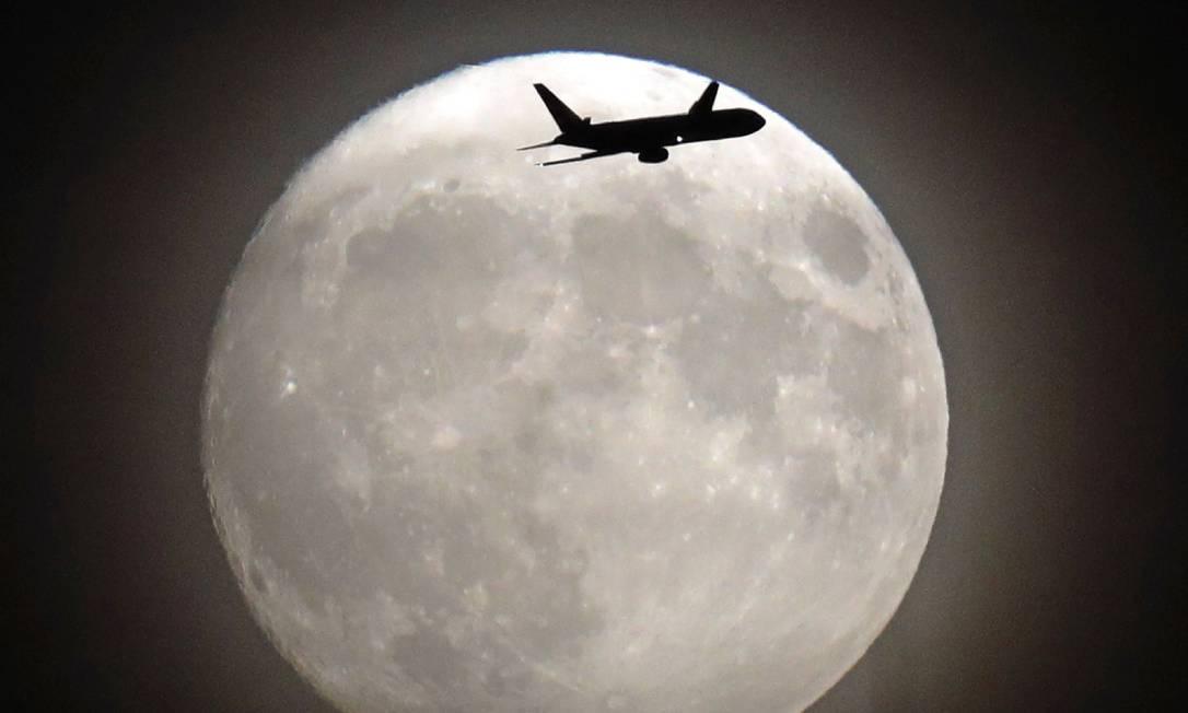 Avião cruza em frente à Lua nas proximidades do aeroporto de Heathrow, em Londres ADRIAN DENNIS / AFP