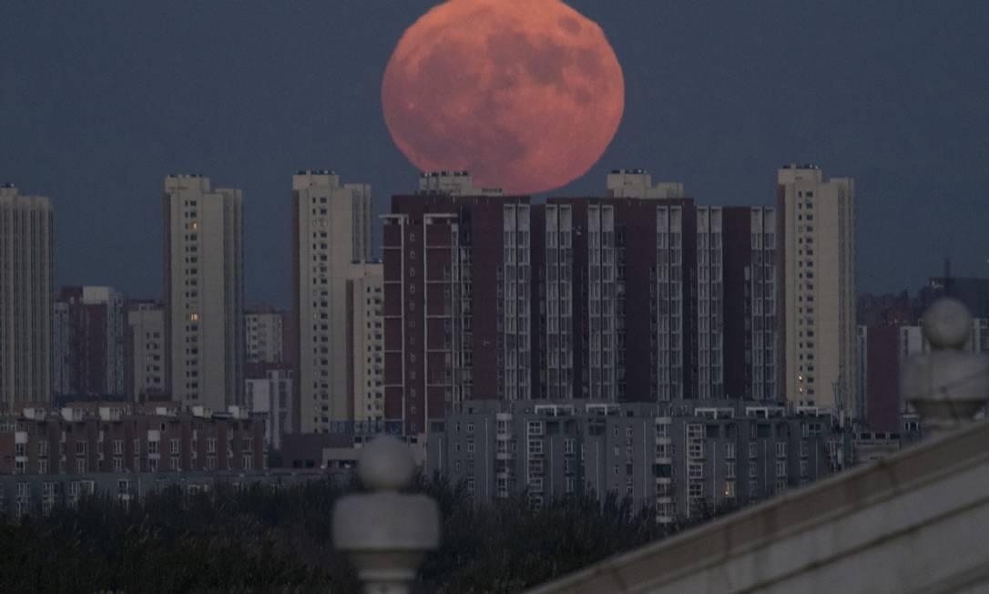 A Lua aparece por trás de edifícios residenciais em Pequim, na China Ng Han Guan / AP