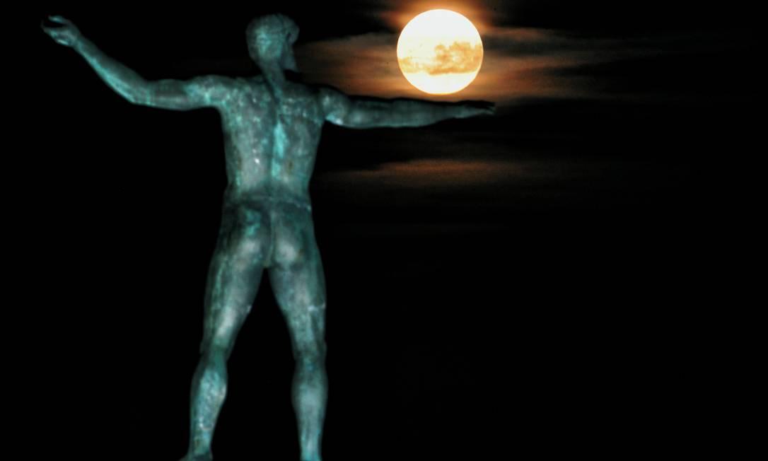A superlua surge acima de uma estátua do deus grego Poseidon, na Grécia VALERIE GACHE / AFP