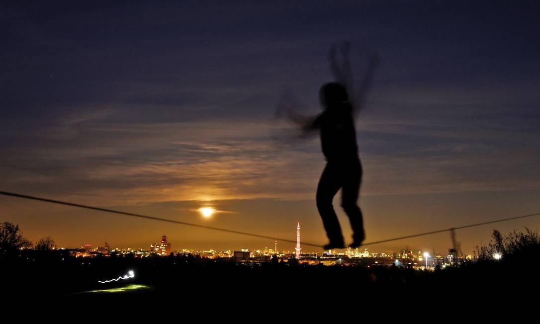 Homem pratica slackline com a Lua ao fundo em Berlim, na Alemanha Rainer Jensen / AP