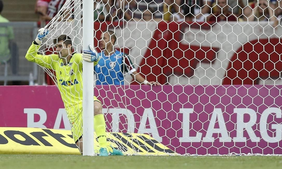 O goleiro do Fluminense, Júlio César, se segura na rede, após salvar um quase gol contra de Gum no jogo com o Atlético-PR Alexandre Cassiano / Agência O Globo