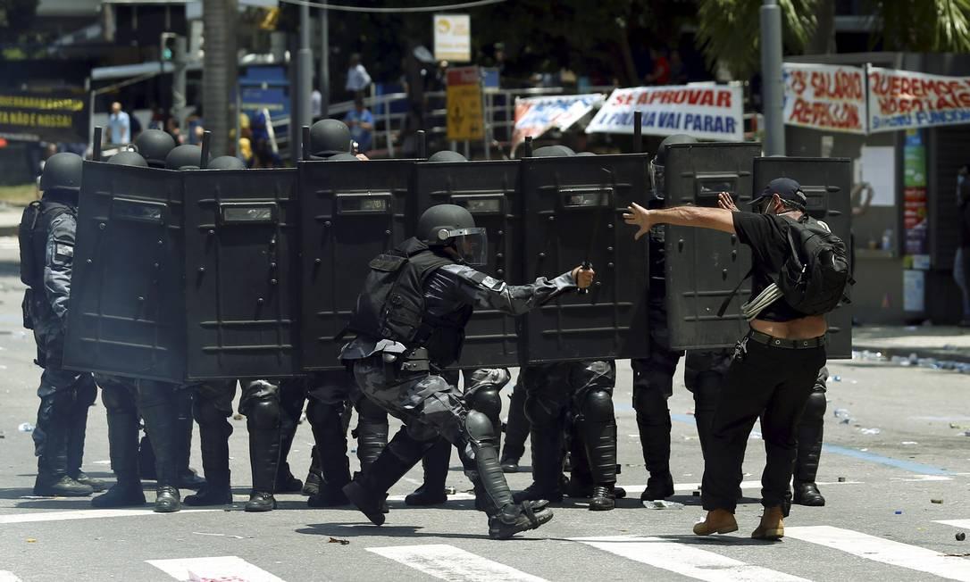Manifestante em frente à barreira de policiais na Rua Primeiro de Março Foto: Gabriel de Paiva / O Globo