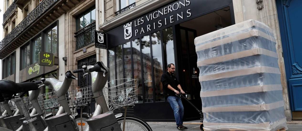 Matthieu Bosser, co-fundador da Les Vignerons Parisiens, carrega garrafas de vinho para serem estocadas em Paris Foto: THOMAS SAMSON / AFP