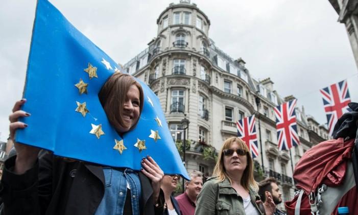 Britânica passeia com o rosto no centro de uma bandeira da União Europeia Foto: CHRIS J RATCLIFFE / AFP
