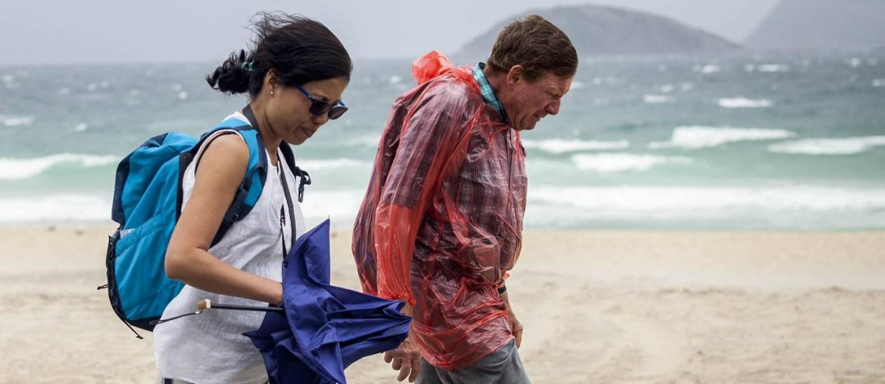 Casal caminha contra o vento na Praia de Ipanema Foto: Hermes de Paula / Agencia O Globo