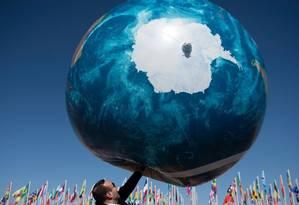Membro de uma delegação brinca com um balão do globo terrestre: países reafirmaram compromisso político com redução das emissões de gases de efeito estufa Foto: FADEL SENNA/AFP