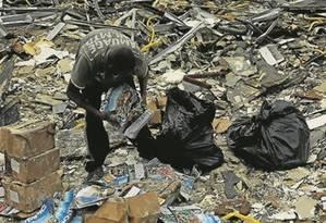 Desperdício. Catador recolhe revistas sobre a Olimpíada que apodrecem a céu aberto Foto: Gabriel de Paiva