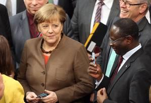 No Parlamento. Diaby (à direita) com Merkel: o deputado de origem senegalesa já enfrentou o preconceito mesmo no Bundestag Foto: WOLFGANG KUMM