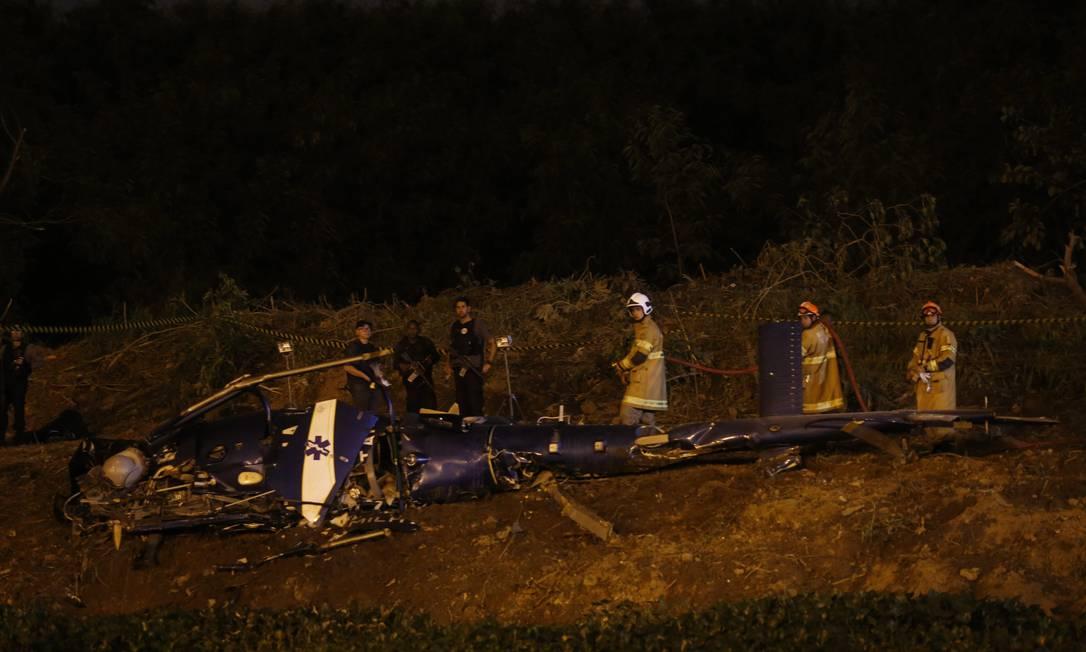 Bombeiros trabalham no local onde houve a queda de helicóptero da PM