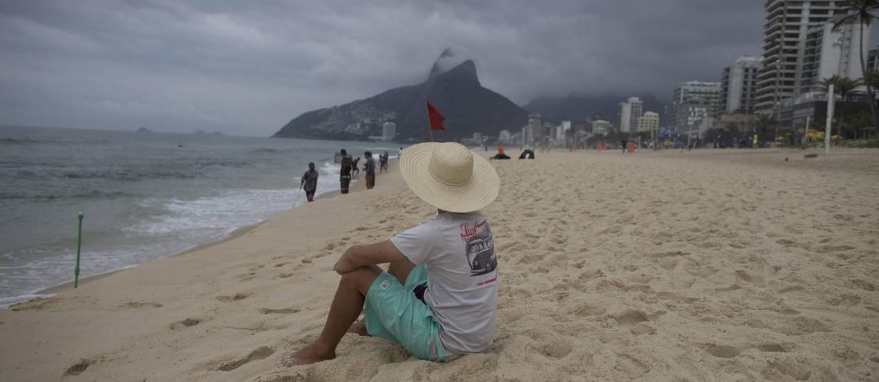 Banhista olha o mar sob o céu encoberto na Praia de Ipanema Foto: Márcia Foletto / O Globo