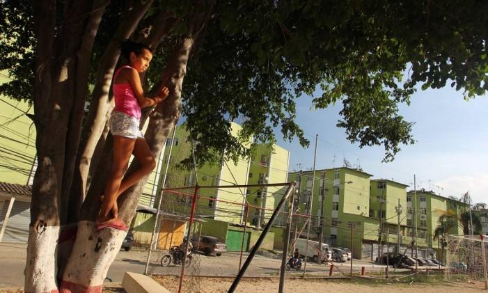 Menina ao lado de quadra de esportes na Cidade de Deus Foto: Márcia Foletto em 18/04/2011 / Agência O Globo