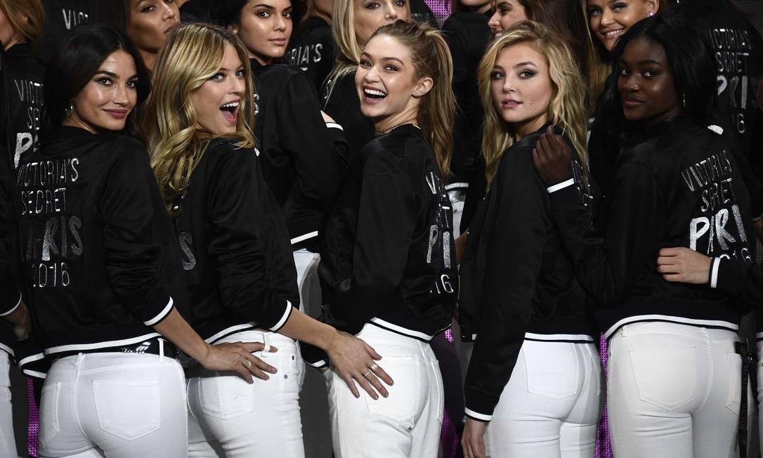 O desfile da Victoria's Secret é só na quarta-feira, mas a grife convocou suas musas para fazer fotos oficiais, no Grand Palais, em Paris, local do show. Na hora do clique de costas, a angel americana Martha Hunt colocou a mão no bumbum de Gigi Hadid MARTIN BUREAU / AFP