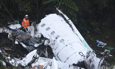 Socorrista trabalha nos destroços do avião Avro da companhia LaMia, que matou integrantes da Chapecoense e jornalistas Foto: Luis Benavides / AP