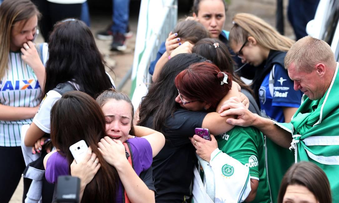 Amigos das vítimas se abraçam na Arena Conda em Chapecó PAULO WHITAKER / REUTERS