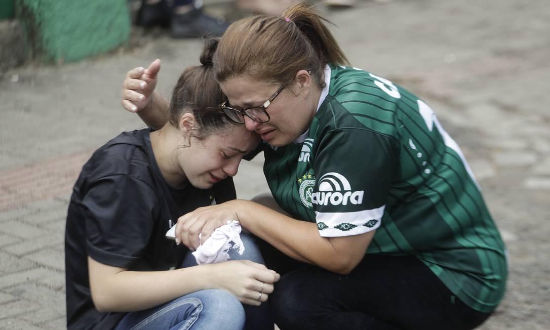 Fã é consolada do lado de fora do estádio Arena Conda, em ChapecóAP Photo/Andre Penner) Andre Penner / AP