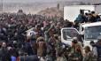 Fuga em massa. Famílias sírias deixam tudo para trás e fogem do Leste de Aleppo em veículos fornecidos pelas forças leais a Damasco: elas são levadas para o Oeste da cidade, controlado pelo regime