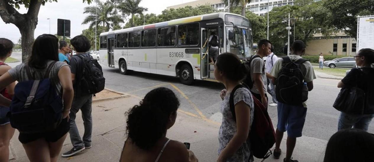 Clima de insegurança. Estudantes em um ponto no campus da Ilha do Fundão: relatos de roubos dentro de ônibus triplicaram nos últimos dois meses Foto: Domingos Peixoto