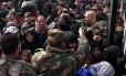 Famílias sírias que fogem de distritos a leste de Aleppo tentam embarcar em ônibus do governo