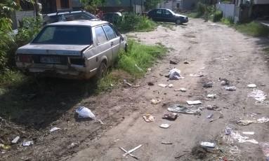 Lixo, carro abandonado e falta de pavimentação na via Foto: Leitora Maria Cecília Mendonça / Eu-Repórter