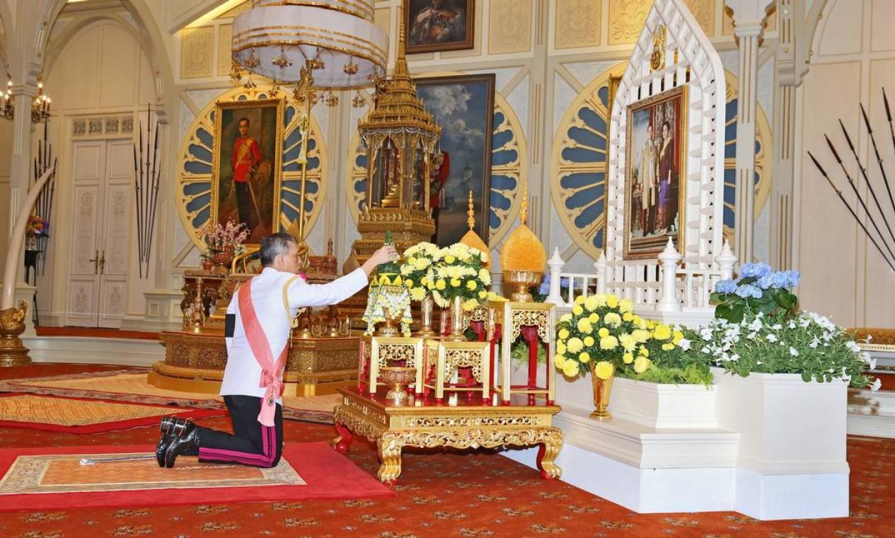 O novo rei da Tailândia, Maha Vajiralongkorn, se ajoelha em frente a um quadro com a imagem de seus pais Bhumibol Addlyadej e Sirikit, no Palácio Dusit, em Bangkok Foto: HANDOUT / REUTERS