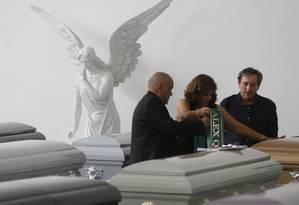 Conselheiro da Chapecoense, Roberto de Marchi observa funcionários da funerária preparem o caixão de uma das vítimas Foto: Antonio Scorza/Agência O Globo