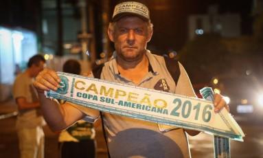 O vendedor ambulante Joel Frankowski comercializa faixas da Chapecoense campeã da Sul-Americana Foto: MARCOSALVES / Marcos Alves/Agência O Globo