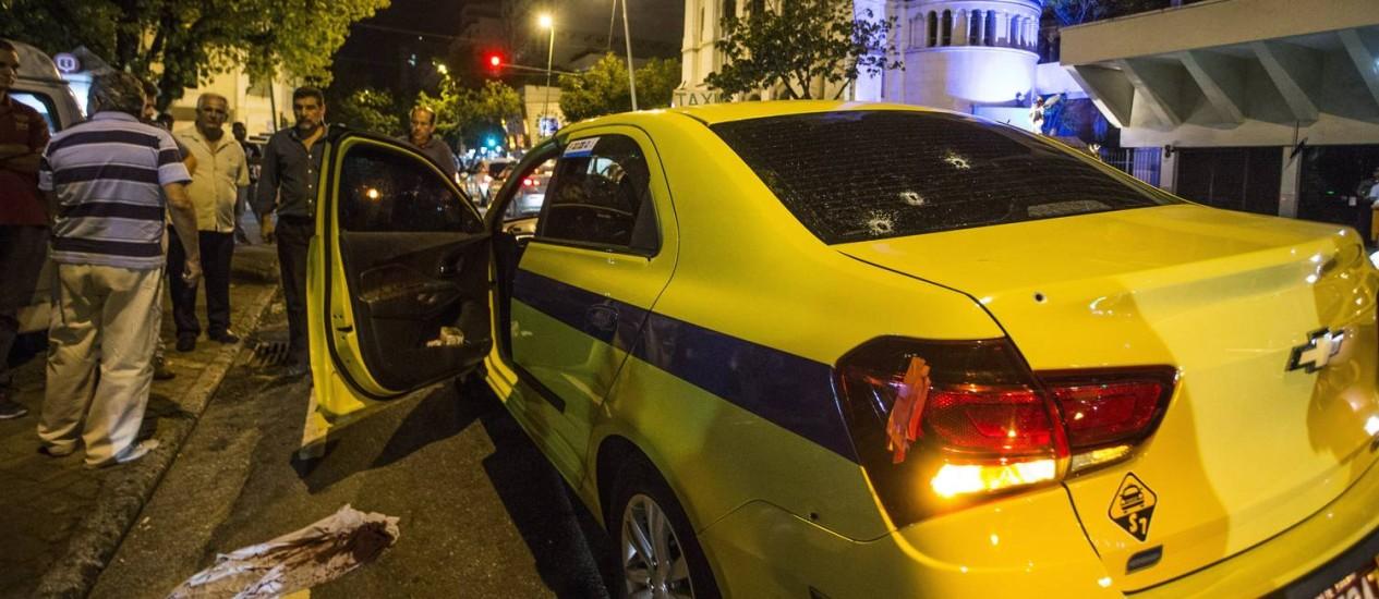 Táxi com marcas de tiros e com camisa ensaguentada abandonado pelos criminosos Foto: Guito Moreto / Agência O Globo