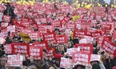 Manifestantes levam placas em protesto pela saída de presidente sul-coreana do poder Foto: Lee Jin-man / AP