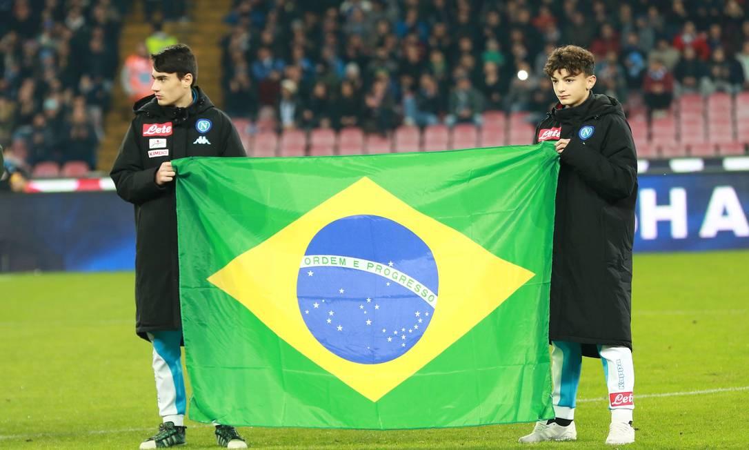 Jovens jogadores do Napoli com uma bandeira do Brasil antes da partida contra a Inter de Milão pelo Campeonato Italiano CARLO HERMANN / AFP