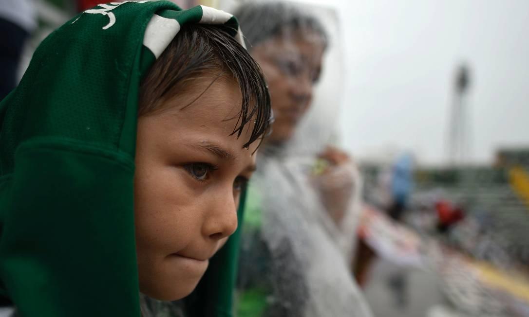 Menino desolado acompanha o velório coletivo DOUGLAS MAGNO / AFP