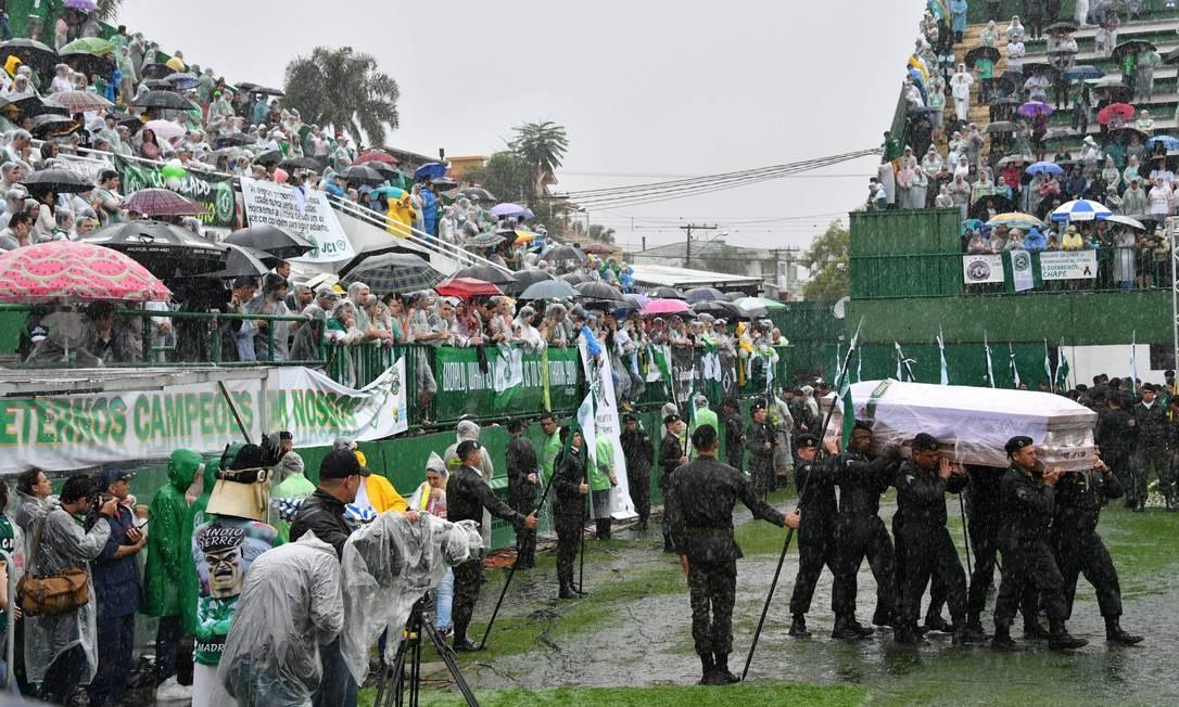Nas arquibancadas, a população de Chapecó se protege da chuva enquanto acompanha o velório NELSON ALMEIDA / AFP