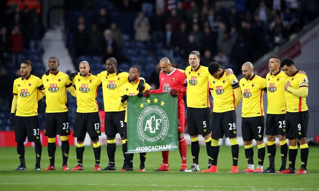 Jogadores do Watford fazem um minuto de silênco em homenagem à Chapecoense. O goleiro brasileiro Gomes é um dos que seguram a bandeira da equipe brasileira Nick Potts / AP