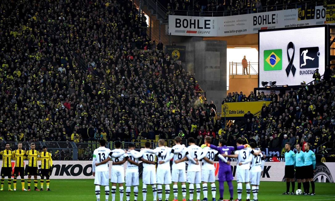 Um minuto de silêncio em homenagem à Chapecoense antes do jogo entre Borussia Dortmund e Borussia Monchengladbach, pelo Campeonato Alemão PATRIK STOLLARZ / AFP