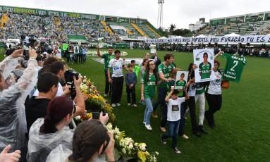 Familiares das vítimas da tragédia do voo da Chapecoense caminham pelo gramado com fotos de jogadores da equipe no fim da cerimônia na Arena Condá Foto: NELSON ALMEIDA / AFP
