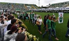 As famílias caminharam pelo campo da Arena Condá exibindo fotos e camisas de seus entes queridos Foto: NELSON ALMEIDA / AFP