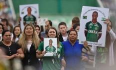 Familiares dos jogadores da Chapecoense exibem fotos e camisas de seus entes queridos Foto: DOUGLAS MAGNO / AFP