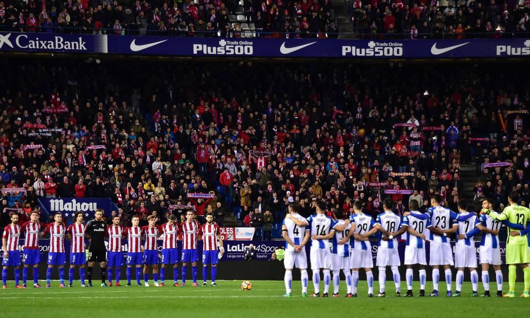 Os jogadores de Atlético de Madrid e do Espanyol fazem um minuto de silêncio em homenagem à Chapecoense GERARD JULIEN / AFP